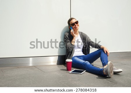 Young happy teen girl using a smart phone over wall in the background - stock photo