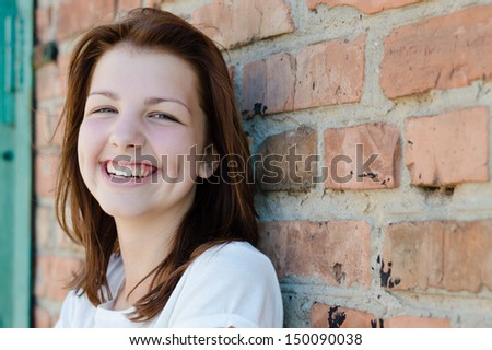 Young happy teenage girl standing at brick wall background copyspace - stock photo