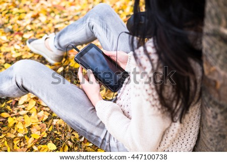 Young happy teenage girl using her tablet and listening to music in autumn city park. Fall life-style picture