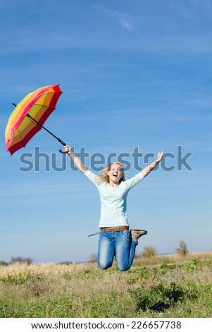 Young happy teenage girl with colorful umbrella jumping high on empty autumn field copy space background