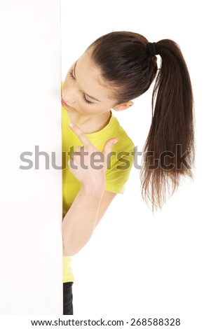Young happy teenage woman pointing on blank board. - stock photo