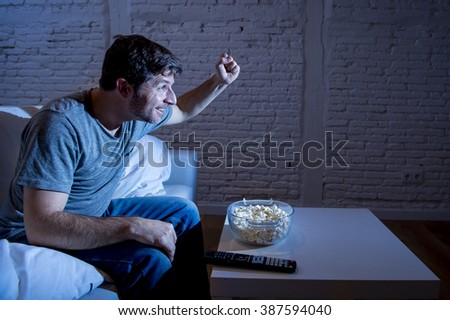 young happy television addict man sitting on home sofa watching TV and eating popcorn looking excited enjoying live sport match celebrating goal or victory - stock photo