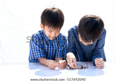 Young happy Thai boy build a tower by a coin on white background