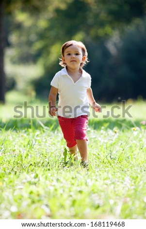 young happy toddler running outdoors in a park