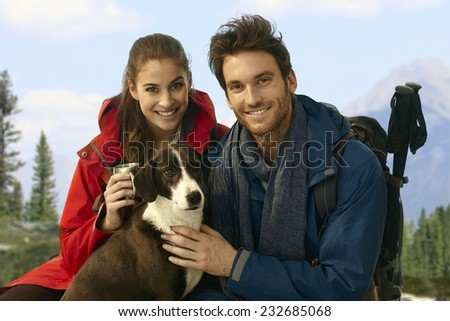 Young happy trekkers with dog taking rest while hiking in mountains.