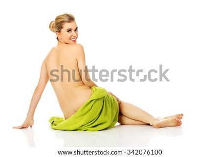 Young  happy woman after bath or spa sitting on the floor wrapped in towel - stock photo