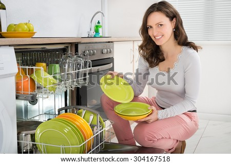 Young Happy Woman Arranging Plates In Dishwasher At Home - stock photo