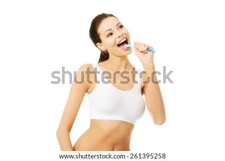 Young happy woman brushing her teeth. - stock photo