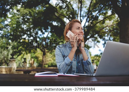 Young happy woman calling with smart phone while taking break between work on laptop computer, smiling female student talking on cell phone while sitting with net-book in park during recreation time - stock photo