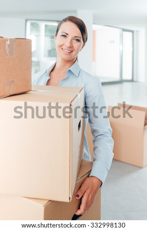 Young happy woman carrying a pile of cardboard boxes in her new office, she is smiling at camera - stock photo