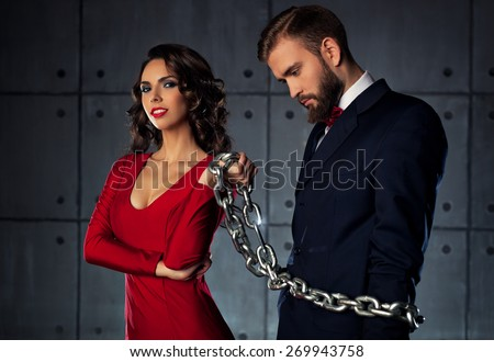 Young happy woman catching man and holding him on heavy chain. Elegant evening clothing. - stock photo