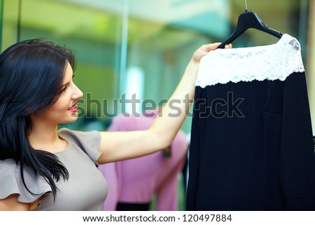 young happy woman chooses dress in clothing store