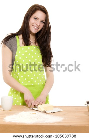 young happy woman cutting butter for baking on white background - stock photo
