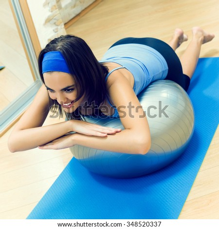 Young happy woman doing fitness exercises with fit ball at home