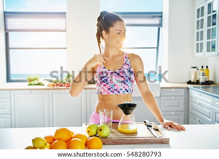 Young happy woman doing fresh with liquidizer at the kitchen. Horizontal indoors shot