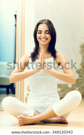 Young happy woman doing yoga exercise at home