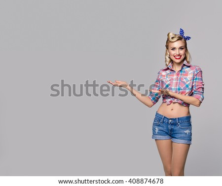 Young happy woman, dressed in pin-up style, showing something or copyspace area for text or slogan. Caucasian blond model posing in retro fashion and vintage concept studio shoot, on grey background. - stock photo