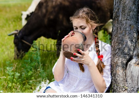 Young happy woman drinking fresh milk near cows in countryside on summer day - stock photo