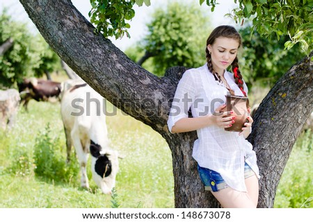 Young happy woman drinking fresh milk near cows in countryside on summer day outdoors background