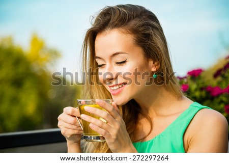 Young Happy Woman Drinking Green Tea Outdoors. Summer Background. Shallow Depth of Field. Healthy Nutrition Concept. - stock photo