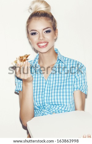 Young happy woman eating a piece of pizza. Indoors, lifestyle. - stock photo
