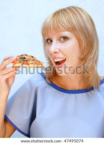Young happy woman eating pizza - stock photo