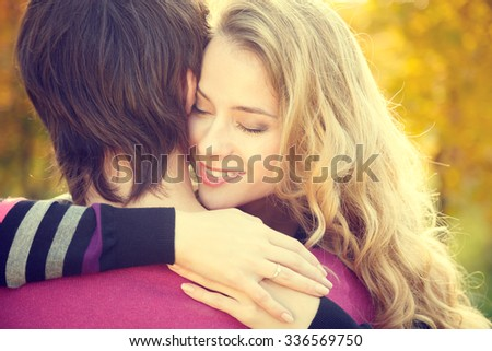 Young Happy Woman Embracing Her Boyfriend on Autumn Background. Dating and Relationship Concept. Toned Photo.  - stock photo