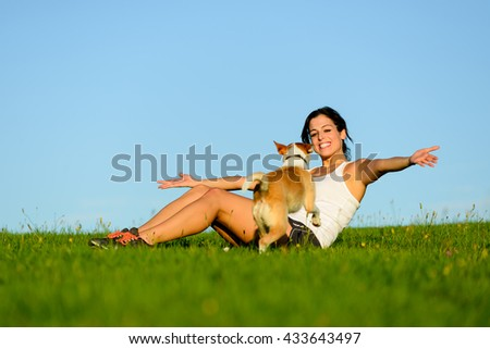 Young happy woman enjoying and having fun with her dog outdoor. Human and pet friendship and leisure healthy activity.