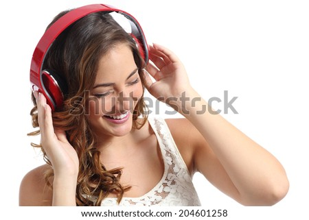Young happy woman enjoying listening to the music from headphones isolated on a white background              - stock photo