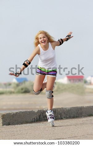 young happy woman enjoying rollerblading / roller skating - stock photo