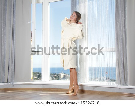 young happy woman enjoying sea view in hotel / room next to big window - stock photo