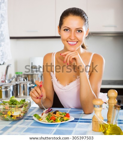 Young happy woman enjoying vegetable salad and smiling