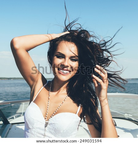 Young happy woman have fun on the luxury boat in open sea in summer. Caucasian latin female model  - stock photo