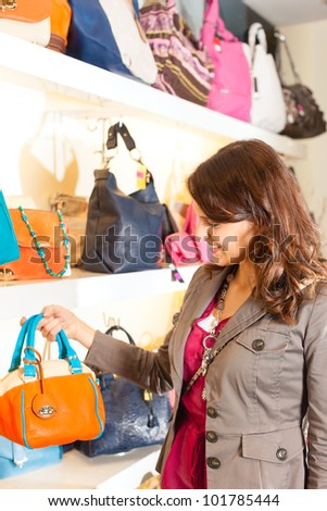 Young happy woman having fun while shopping in a mall, she is looking for a bag - stock photo
