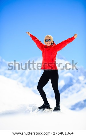 Young happy woman hiker portrait on mountain peak summit in winter mountains. Climbing inspiration and motivation, beautiful landscape. Fitness healthy lifestyle outdoors on snow in Himalayas, Nepal. - stock photo