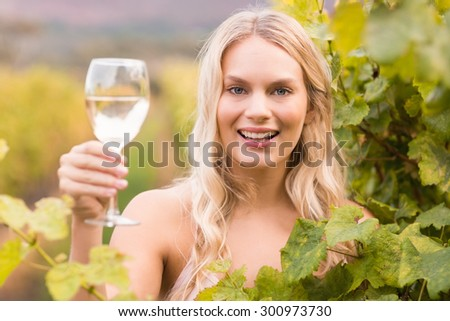Young happy woman holding a glass of wine in the grape fields