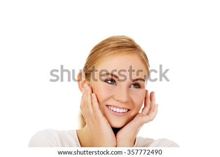Young happy woman holding both hands on cheeks.