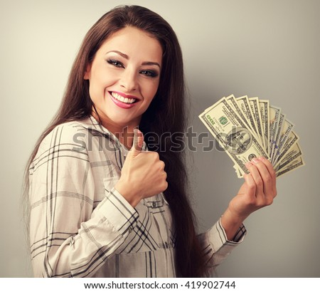 Young happy woman holding dollars and showing thumb up sign. Toned portrait - stock photo
