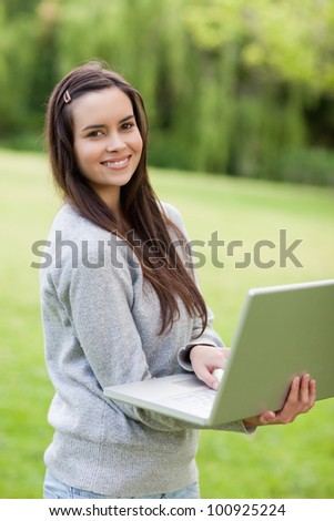 Young happy woman holding her laptop while standing in a parkland and smiling