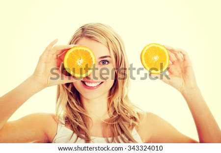 Young happy woman holding oranges - stock photo