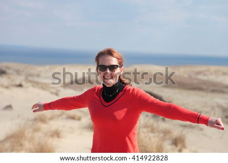 Young happy woman in a red sweater and sunglasses on the seashore - stock photo