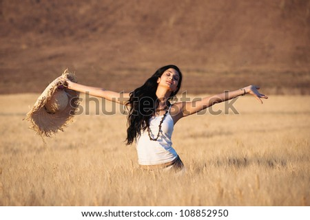 Young happy woman in a wheat field with white dress and straw hat. - stock photo
