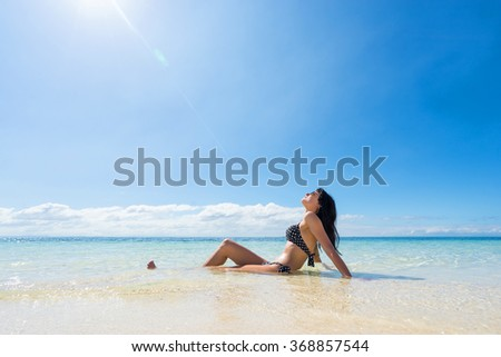 Young happy woman in black  bikini enjoys sunny day on beach. Tropical vacation  - stock photo