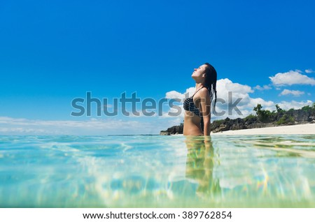 Young happy woman in black bikini enjoys sunny day on the sea. Tropical vacation