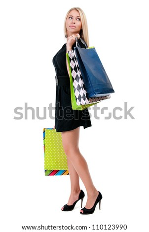 Young happy woman in black dress with colorful shopping bags on a white background - stock photo