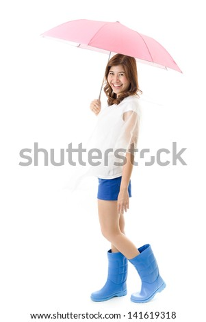 Young happy woman in blue boots with raincoat holding umbrella on white background. Raining season and water flood concept.