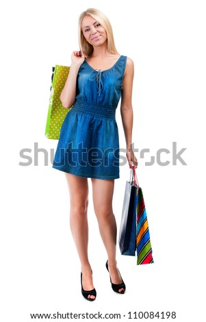 Young happy woman in blue dress with colorful shopping bags on a white background