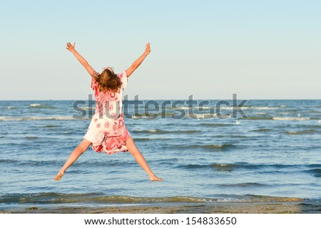 Young happy woman in funky dress jumping high at seaside on the summer outdoors background