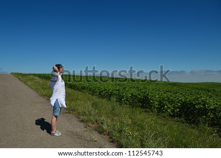 Young happy woman in green field with blue sky in background