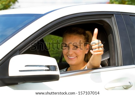 Young, happy woman in her new car with thumb up - stock photo
